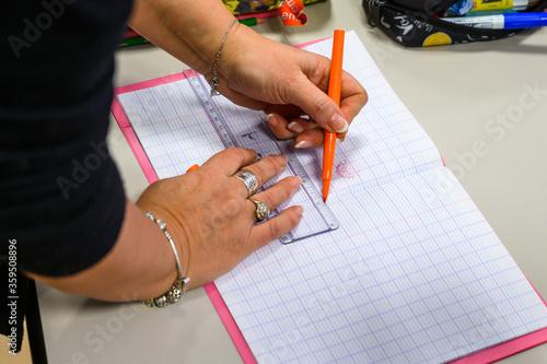 Fotografía L'institutrice indique les consignes sur le cahier de l'élève