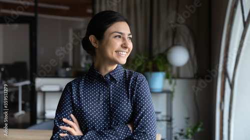 Fototapeta Successful Indian businesswoman, promoted employee headshot. Confident lady boss with arms crossed standing in modern office looking out the window feels proud by achievement, business goes up concept obraz na płótnie