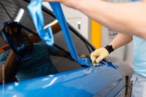 Photo Mechanic hands installs car foil or film