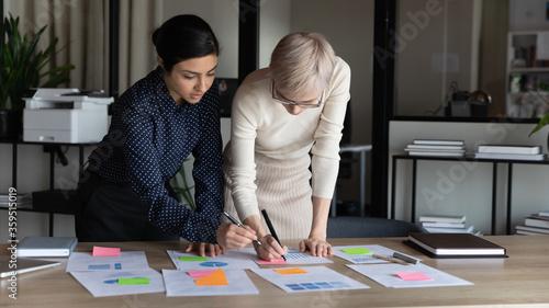 Fotografía Multiracial businesswomen work on project statistics, prepare financial report u