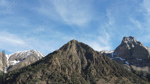 Three Mountain Peaks in Mid Spring with Light Coat of Snow and Blue Sky Clouds