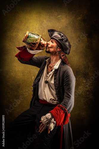 Fotografie, Obraz Portrait of a pirate in profile, drinking rum from a jug