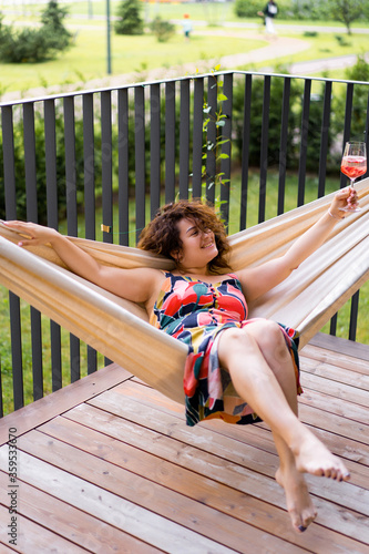 Fototapety, obrazy: young beautiful woman with curly hair drinks summer lemonade in a hammock, happy smile. Relax on the terrace in a hammock with a glass of fruit lemonade with strawberries.