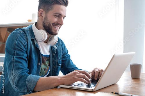 Handsome modern man designer working on laptop online, using internet at home Canvas
