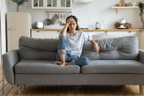 Tired upset woman worried about tiredness from domestic work sitting at couch Canvas Print