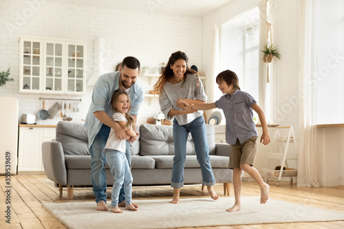 Obraz na plátně Happy family playing funny game having fun together with little son and daughter in modern living room