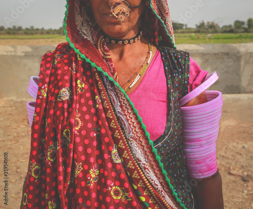 Fotografija Helf face of Indian Rajasthani woman wearing traditional colourful clothing and