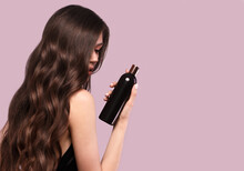 Beautiful Brunette Woman With Curls And Classic Make-up In A Black Dress With A Bottle Of Shampoo In Hands. Beauty Face.