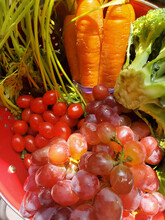 Fresh Fruits And Veg - Grapes Tomatoes Carrots And Broccoli In Red Metal Colander - Selective Focus