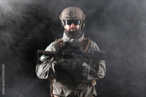 Fotomural portrait of a commando in uniform with weapons against a dark background, elite