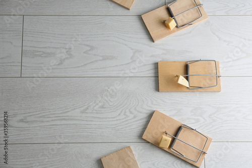Fotografía Mousetraps with pieces of cheese and space for text on white wooden background, flat lay