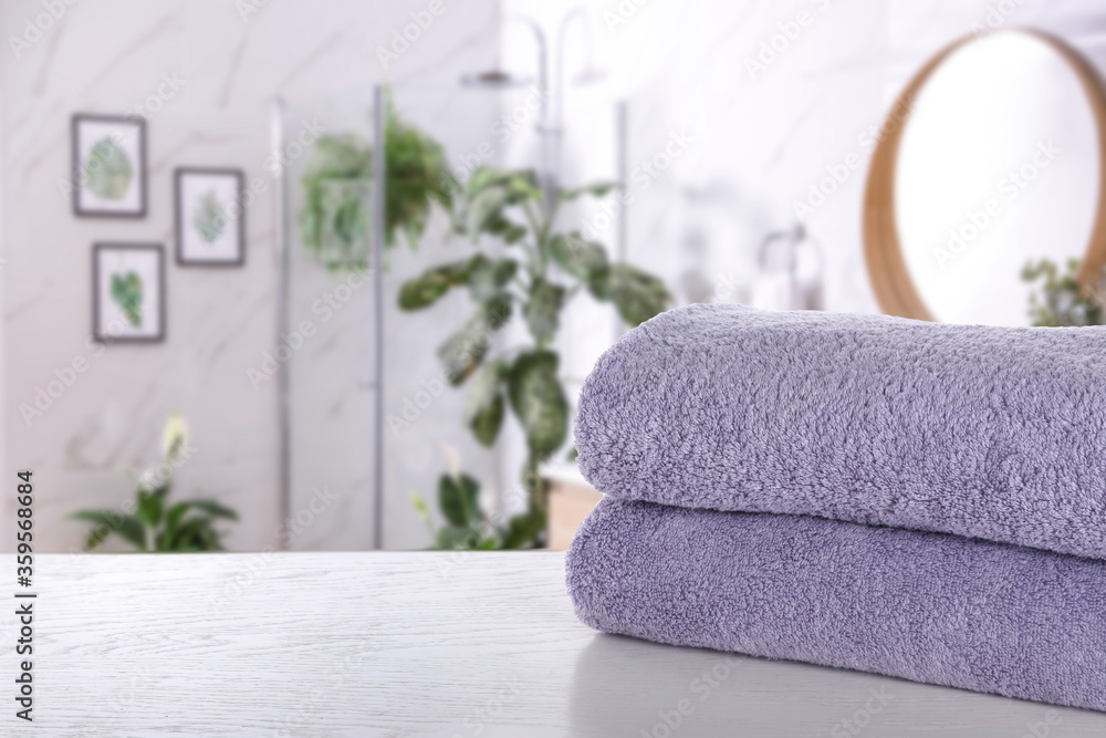 Fototapeta Fresh towels on white wooden table in bathroom. Space for text