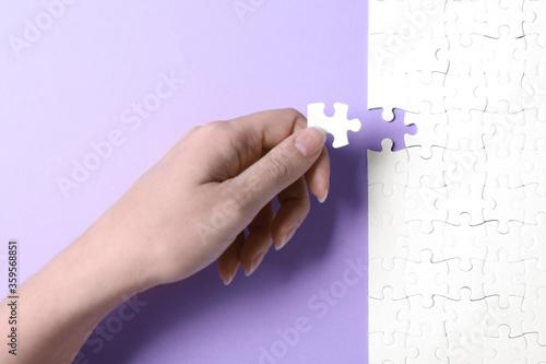 Woman putting last piece of white puzzle on violet background, closeup Billede på lærred