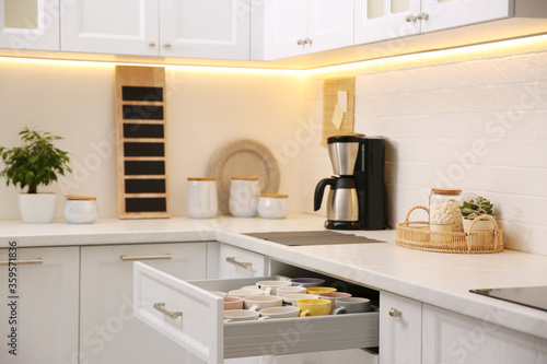 Wallpaper Mural Open drawer with cups and coffeemaker on countertop in kitchen