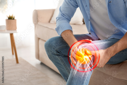 Fotomural Man suffering from knee pain at home, closeup