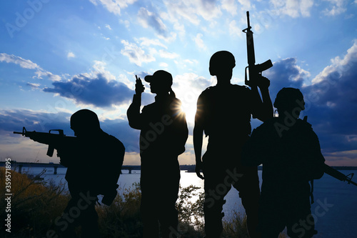 Fotografering Silhouettes of soldiers with assault rifles and portable radio transmitter patrolling outdoors