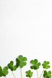 Clover leaves on white wooden table, flat lay with space for text. St. Patrick's Day symbol