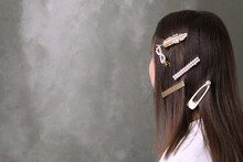 Young Woman With Beautiful Hair Clips On Grey Background, Space For Text