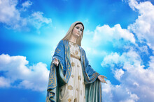 Our Lady Of Grace Virgin Mary With Bright Blue Sky And Beautiful Clouds With Abstract Colored Background And Wallpaper