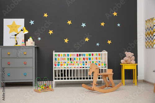 Cute baby room interior with modern crib and rocking horse