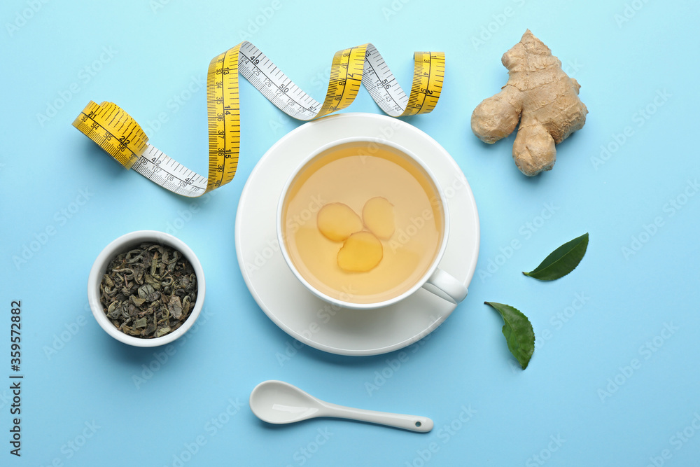 Fototapeta Flat lay composition with cup of diet herbal tea and measuring tape on light blue background