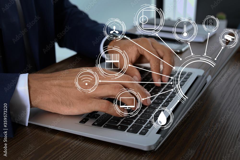 Fototapeta Man using laptop to control smart home, closeup. Automatic systems