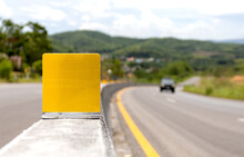 Closeup Reflective Traffic Sign On Concrete Barrier In The Road With Soft-focus And Over Light In The Background