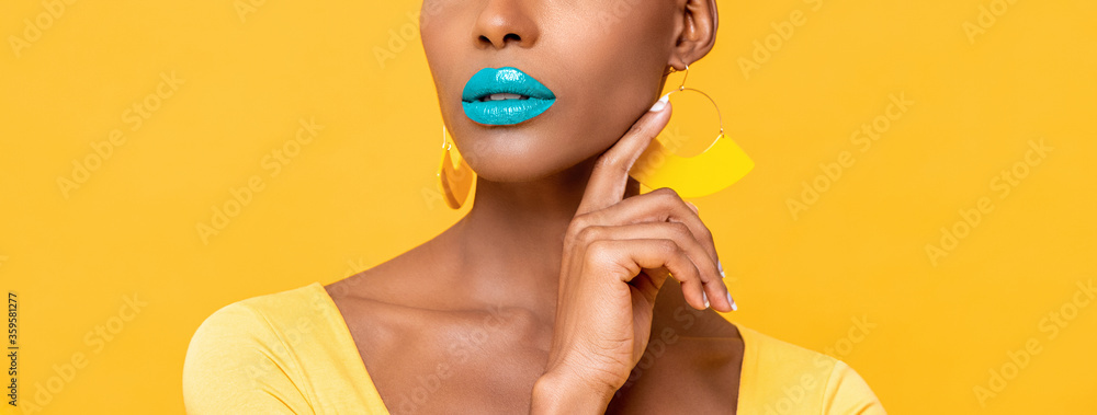 Fototapeta Close up panoramic portrait of  beautiful African American woman with blue lip makeup touching her face   isolated studio yellow background