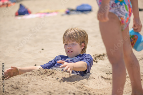 Valokuva Portrait of a boy playing on the beach buried in the sand