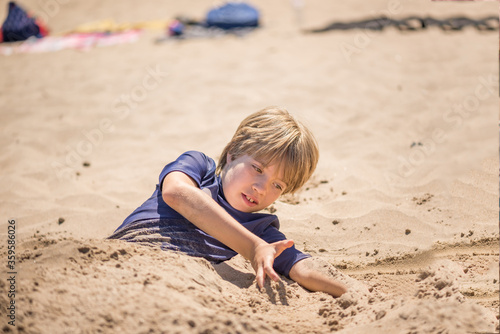 Portrait of a boy playing on the beach buried in the sand Canvas-taulu