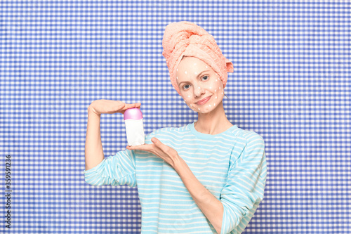 Happy girl with problem face skin is holding deodorant in bathroom Canvas Print