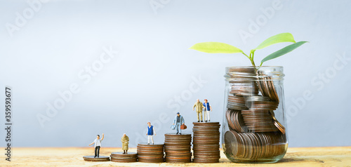 Valokuva Miniature people standing on stack of coins