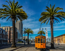 Old Orange San Francisco Cable Car On The Embrcadero With The Ferry Building And Palm Trees In The Background