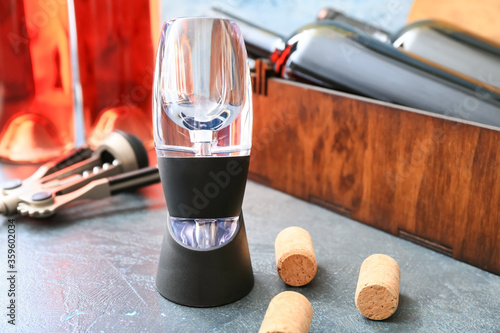 Photo Wine aerator with bottles on color background