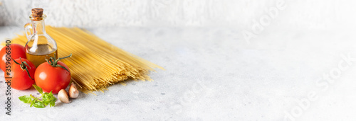 Foto Dry Spaghetti bunch , fresh tomatoes, basil, garlic and olive oil on large background for banner