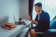 Young Asian Businessman wear Formal Suit with Short Pants Having Video Conference Meeting with Business Partner on Sofa at Home in Living Room during Quarantine Period.