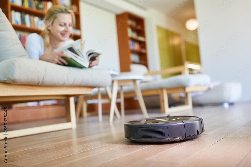 Fototapeta Vacuum robot automatically cleans parquet floor