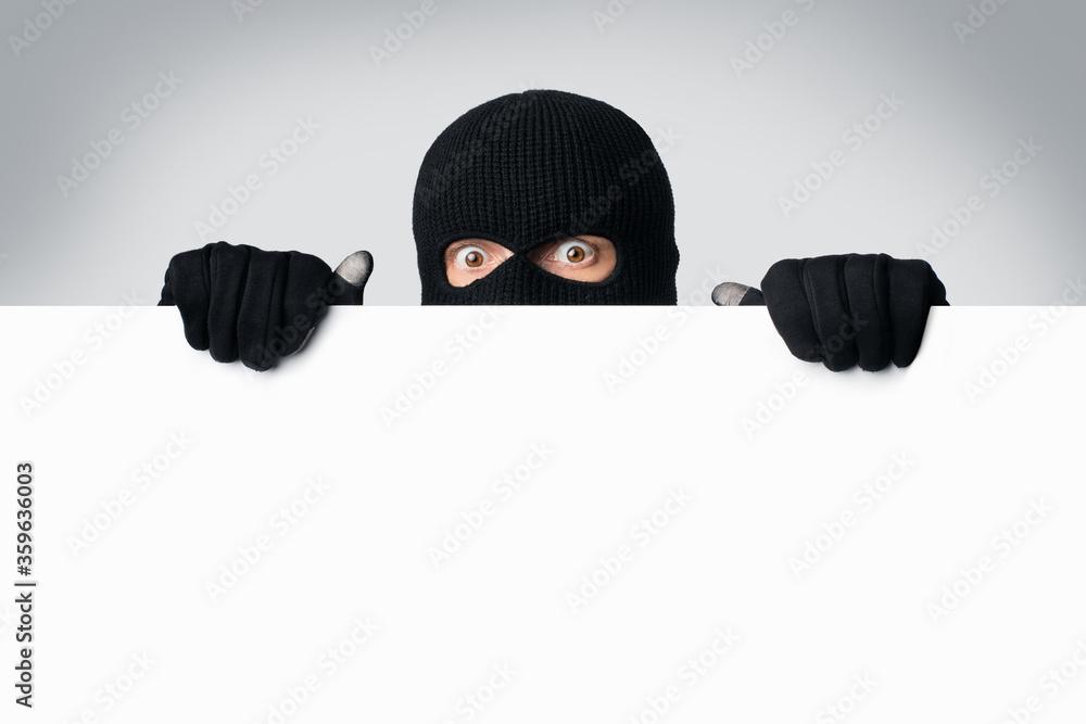 Fototapeta Masked thief peeking out white blank board