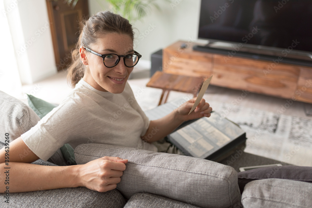 Fototapeta Woman relaxing on the sofa and watching pictures in the photo album