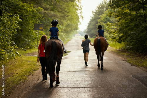 Little girls ride beautiful horses on the road in the forest in summer Wallpaper Mural
