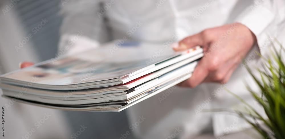 Fototapeta Female hands holding magazines