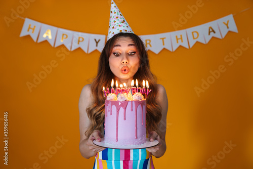 Valokuva Image of happy young woman blowing out candles on birthday torte