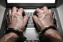 Hands In Handcuffs Typing On L...