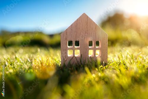 Fotografija Ecological wood  model house in empty field at sunset