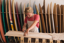 Caucasian Male Surfboard Maker Cutting Wooden Stripes And Surfboards In The Background