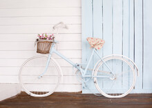 White Bicycle With Beautiful Flower Basket On Vintage Background