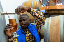 Black African American Man Filling Beer In Glass At Microbrewery