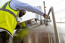 African American Man Working And Looking Inside The Beer Tank In A Brewery