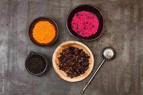 Surtido de té seco dentro de cuencos sobre un fondo de metal rústico y oscuro junto a un infusor Tablou Canvas