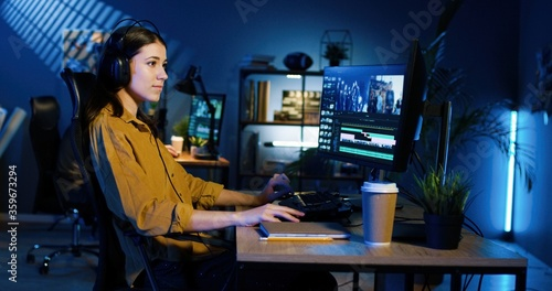 Picture of professional female video editor editing video on his personal computer with two displays in modern video studio.